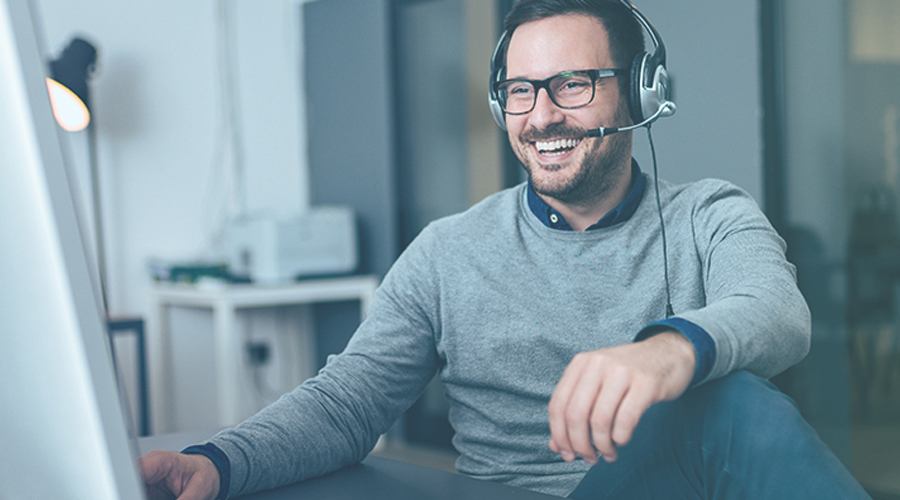 Image of Man smiling at laptop with headphones